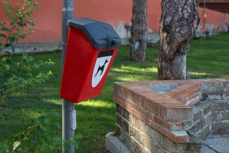 Red plastic bin for dog poo in the park. Image of dog on the container. Concept of clean environment.