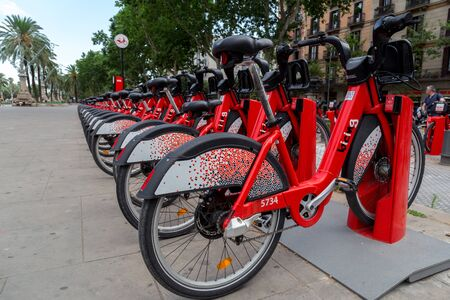 Barcelona, Spain - July 9, 2019: Red bicycles available for rent parked in a row at Passeig de Lluis Companys. Concept of environmentally sustainable transport. Bike rental service Bicing. Close up. 에디토리얼