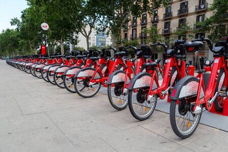 Barcelona, Spain - July 9, 2019: Bright red bicycles available for rent parked in a row at Passeig de Lluis Companys. Concept of environmentally sustainable transport. Bike rental service Bicing. 에디토리얼