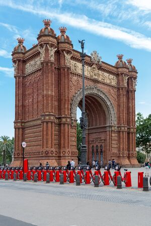 Barcelona, Spain - July 9, 2019: Famous Triumphal Arch (Arc de Triomf) on blue sky background. Sunny summer day, tourists walking around, bright red bicycles available for rent ( «bicing» service )