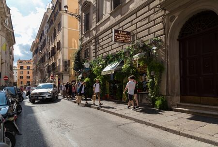 Rome, Italy - September 29, 2019: Typical old Roman narrow street. Lovely Italian restraunt, walking people, parked cars, ancient houses on blue sky background.