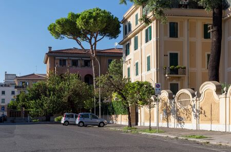 Rome, Italy - September 29, 2019: Lovely quiet street on Aventine hill. Parked cars, beautiful Italian stone pines near houses on blue sky background. No people. 에디토리얼