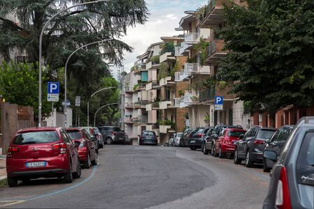 Rome, Italy - September 28, 2019: Lovely quiet street on Aventine hill. Parked cars, beautiful green trees and bushes near houses on blue sky background. No people.
