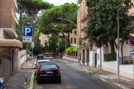 Rome, Italy - September 28, 2019: Lovely quiet street on Aventine hill. Parked cars, beautiful Italian stone pines, green bushes near houses on blue sky background. No people.