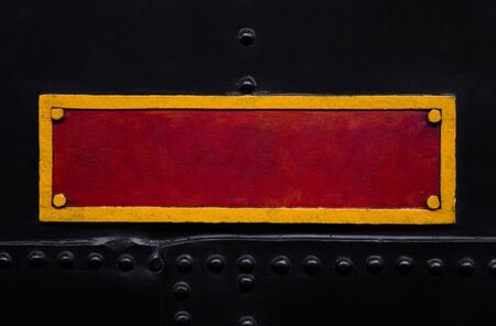 Vintage red and yellow metal plate on the old train.   Textured background. Close shot. Can be used as a retro frame, mockup, template.