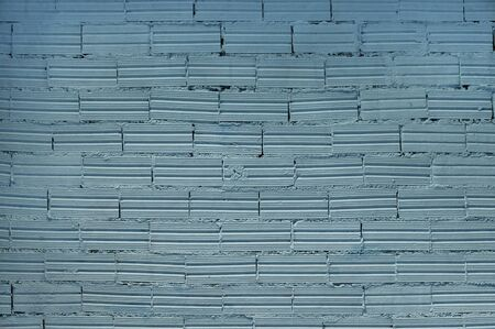 Brick wall background. Decorative bricks with interesting texture and cement joints are covered with light blue paint.