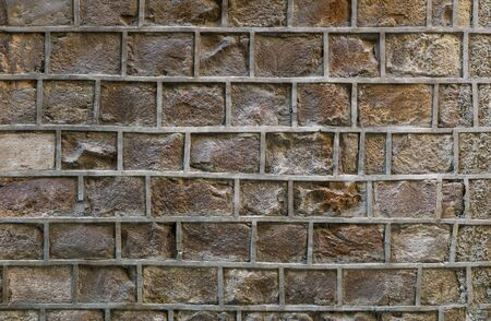 Old stone wall with uneven decorative joints. Unusual brick wall background.