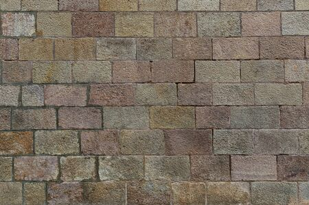 Brick wall background. Old brickwork with multicolor bricks in tints of pink, yellow, green. Close shot.