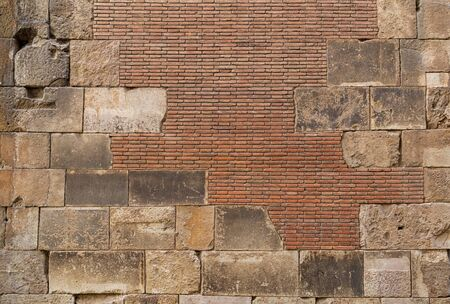 Old brick wall background. Ancient brickwork combined with big stone blocks. The photo was taken in Old town of Barcelona, Spain. 스톡 콘텐츠