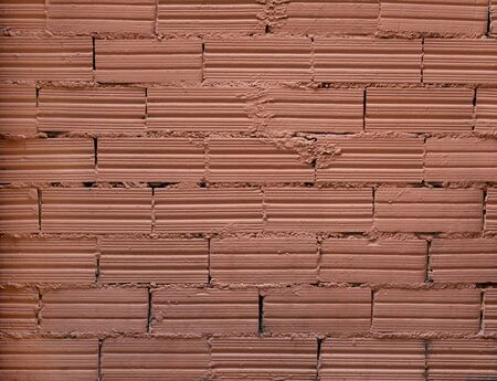 Brick wall background. Decorative bricks with interesting texture and cement joints are covered with coral paint. Close shot.