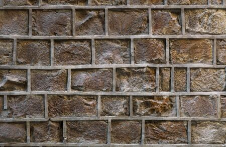 Old stone wall with uneven decorative joints. Unusual brick wall background. Clo se shot.
