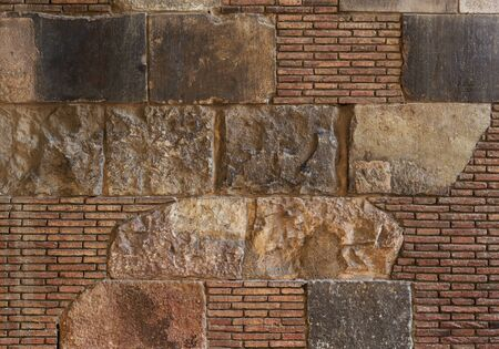 Old brick wall background. Ancient brickwork combined with big stone blocks and rocks. The photo was taken in Old town of Barcelona, Spain.