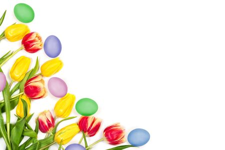 Beautiful Easter floral mockup. Red and yellow tulips and painted eggs on white background. Space for your text. Top view. Flat lay. Can be used as a greeting card.
