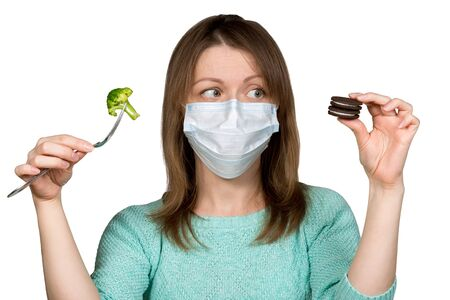 Young woman in face mask is choosing between sweets and broсcoli. Concept of healthy eating during quarantine and self-isolation. Close shot. Isolated on white background.