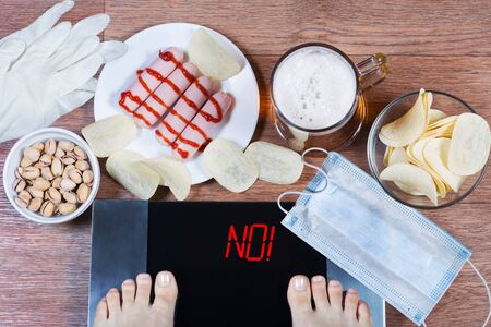 Girl checks her weight after quarantine. Digital scales with word no on screen. Beer, plates with junk food, face mask and gloves on the floor. Concept of unhealthy lifestyle during self-isolation.