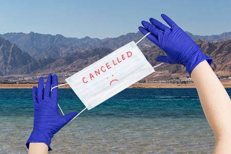 Woman hands with latex gloves on them are holding safety mask with sign cancelled  against beautiful seaside background. Concept of trips cancellation because of coronavirus pandemic. 스톡 콘텐츠