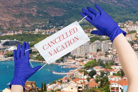 Woman hands with latex gloves on them are holding safety mask with sign cancelled vacation against Montenegro seaside background. Concept of trips cancellation because of coronavirus pandemic. 스톡 콘텐츠