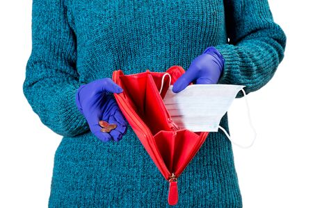 Woman holding empty red wallet and some coins in her hands. Safety mask instead of money. Concept of poverty and financial crisis as a result of covid-19 pandemic and quarantine. Isolated on white. 스톡 콘텐츠