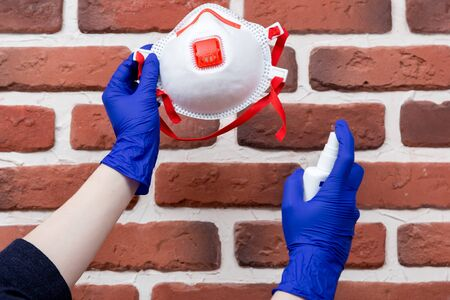 Woman in latex gloves is cleaning her disposal respirator using sanitizer. Reusing of respirators in the context of their deficit and high cost. Brick wall background.