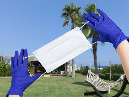 Woman hands with latex gloves on them are holding safety mask against beautiful resort background. Mockup, space for your text. Concept of trips cancellation because of coronavirus pandemic. 스톡 콘텐츠