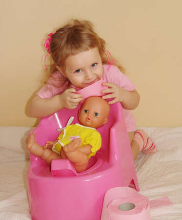 The kid sits on a pot with a toilet paper                                photo