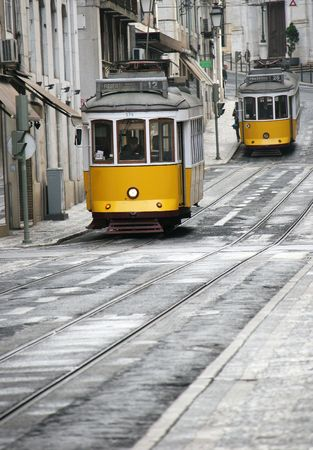lisbon: Two old yellow trams in street of Lisbon