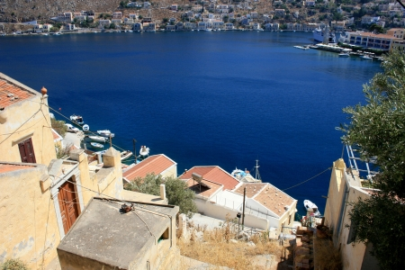 Blue bay and colorful houses in Symi island of the Dodecanese, Greece Stock Photo - 16188142