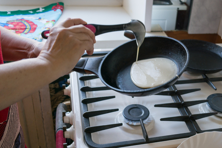the dough spreads in a pan for baking pancakes in the hands of an elderly woman