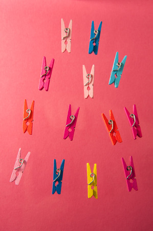 colored clothespins on a pink background Stock Photo