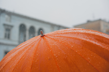 rain drops falling from a big orange umbrella