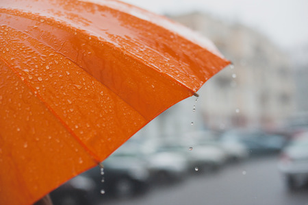 rain drops falling from a bright orange umbrella Reklamní fotografie
