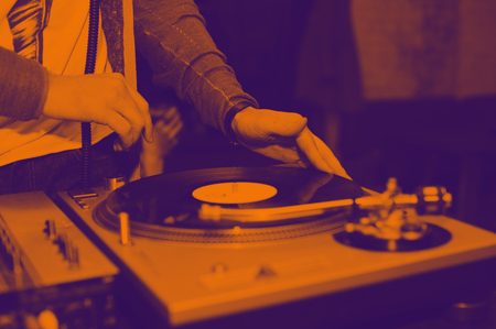 Dj mix tracks at party on vinyl record player. The Duotone effect - orange and purple Stock Photo