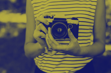 Photo film camera in the hands of the girl. Duotone effect - yellow and blue colors