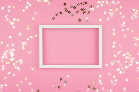 White picture frame and sequins stars on pink background. Top view, flat lay. Mockup for party or birthday invitation.