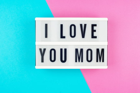 I love you Mom - text on a display lightbox on blue and pink bright background.