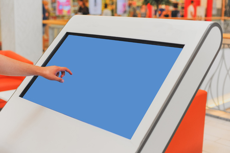 Mockup of digital white screen panel and mans hand. Blank modern media billboard in the shopping center. Place for text, advertising or public information.