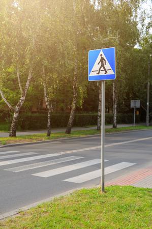 Crosswalk or zebra crossing and street sign.