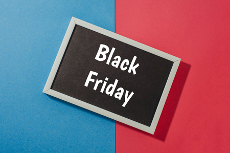 Black Friday - text on chalkboard on blue and red background.