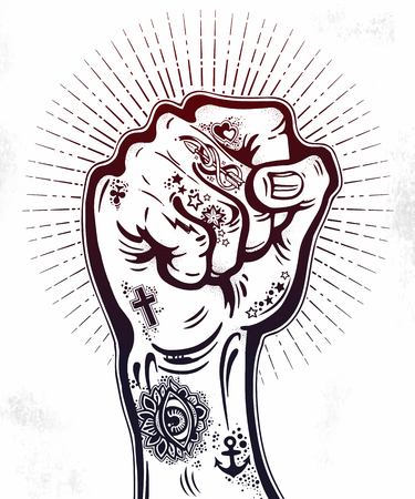 Raised tattooed male hand as a fist power gesture.