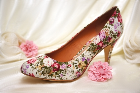accesories: High heeled shoe surrounded by light pink flowers and white velvet. A romantic setting that screams WEDDING.