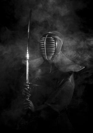 samourai: Kendo samouraïs en armure debout dans la fumée avec l'épée qui brille