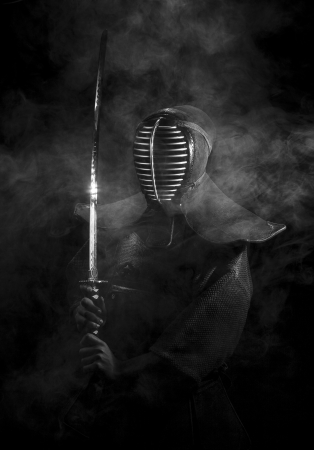 samurai: Kendo samurai in armor standing in the smoke with shining sword