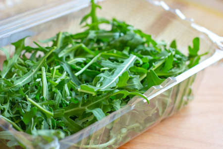 Fresh healthy green arugula leaves in plastic container on light wooden background. Banque d'images