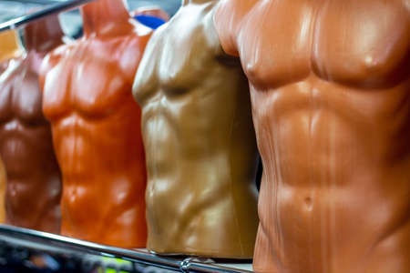 Many different plastic male mannequins in the clothing shop
