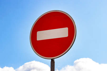 Red and white Do not enter sign on blue sky background.