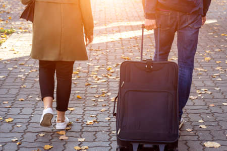 Close up back view of a woman and a man holding suitcase baggage walking on the street in the sunny morning in the autumn while going to airport for travel vacation trip on a modern city background.