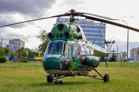 Green military helicopter is landing in the city street park. Reklamní fotografie