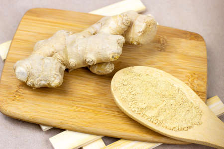 Fresh raw yellow ginger root with ground dry powder in wooden spoon and on wood background. Reklamní fotografie