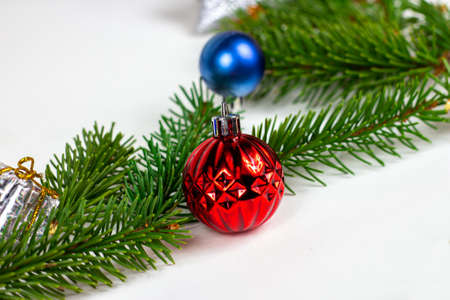 New year and christmas decoration with green fir tree branches and blue and silver shiny xmas traditional balls and baubles for greeting invitation cards.
