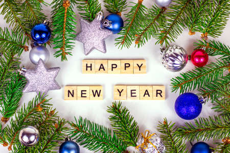 Happy New Year text sign and Christmas decoration with green fir tree branches and blue and silver shiny xmas traditional balls and baubles for greeting invitation cards.